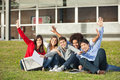 Students with hands raised sitting at university portrait of cheerful on grass campus Royalty Free Stock Photos