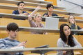 Students having a lesson in the lecture hall taking an active part while sitting Stock Photo
