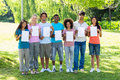 Students holding blank papers group portrait of college on campus Stock Image