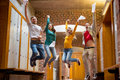 Students jumping in college corridor full length of a group of Royalty Free Stock Images