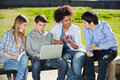 Students with laptop and mobilephone sitting in young university campus Royalty Free Stock Photography