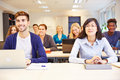 Students learning in university class many smiling a Royalty Free Stock Photo