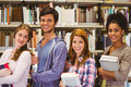 Students in a line smiling at camera holding books library Royalty Free Stock Photography