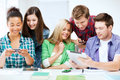 Students looking at smartphones and tablet pc education technology internet Stock Images