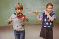 Students playing flute and violin in classroom portrait of cute little Stock Photo
