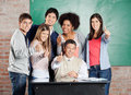 Students and professor gesturing thumbsup at desk portrait of happy multiethnic in classroom Stock Photography