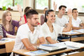 Students raised hands in classroom answering on questions with Royalty Free Stock Image