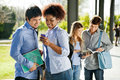 Students reading text message on mobilephone in young college campus Royalty Free Stock Photos