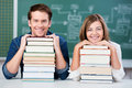Students resting chin on stack of books at desk portrait male and female classroom Royalty Free Stock Photo