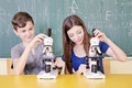 Students in science class using a microscope Royalty Free Stock Photos