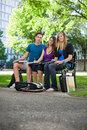 Students sitting on campus bench portrait of completing assignment at Stock Photography