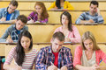 Students sitting at the lecture hall while writing concentrating Royalty Free Stock Photos