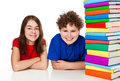 Students sitting next to pile of books Royalty Free Stock Images