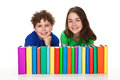 Students sitting next to pile of books Royalty Free Stock Photo