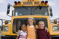 Students Standing In Front Of School Bus Stock Image