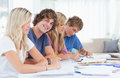 Students studying together with one man looking at the camera  Royalty Free Stock Photos