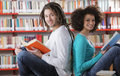 Students two learning together indoors in library Stock Photography