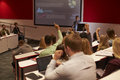 Students at university lecture raise hands to ask questions Royalty Free Stock Photo