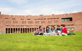 Students using laptop in lawn against college building Royalty Free Stock Photo