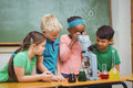 Students using science beakers and a microscope at the elementary school Royalty Free Stock Images