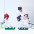 Students working in chemistry lab close up of a teacher a supervising the activity on two analyzing plants on a table and Stock Photography