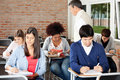 Students writing exam while teacher supervising group of multiethnic them in classroom Stock Image