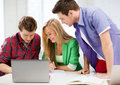 Students writing test or exam in lecture at school education and internet smiling Royalty Free Stock Photo