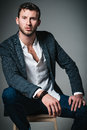 Studio fashion shot: portrait of handsome young man in jeans, shirt and jacket sitting on bench Royalty Free Stock Photo