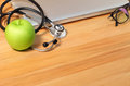 Studio macro of a stethoscope apple pen eyeglass and notebook wi with shallow dof evenly matched abstract on wood table background Stock Photos