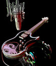Studio music microphone above an electric guitare and headphones resting on it Royalty Free Stock Photos