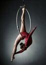 Studio photo of acrobatic girl dancing with hoop on grey background Royalty Free Stock Photo