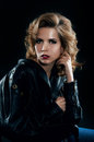 Studio portrait of blonde woman in leather biker jacket Imagens de Stock Royalty Free