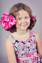 A studio portrait of a smiling pretty girl in a pink dress and with a pink flower in her hair Stock Photography