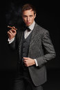 Studio portrait of young man smoking a cigar Royalty Free Stock Photo