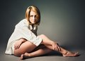 Studio shot beautiful young girl in white shirt sits on the floor a Royalty Free Stock Photo
