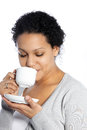 Studio shot of dark skinned lady enjoys her coffee isolated on white Royalty Free Stock Images