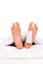 Studio shot of a dead body with a toe tag isolated on white background Royalty Free Stock Photos