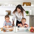Studio shot of a family in the kitchen at home. Small children, a girl and a boy, learn to make dough rolls with their mother or Royalty Free Stock Photo