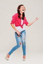 Studio shot of happy woman playing air guitar Stock Images