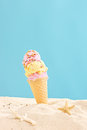 Studio shot of an ice cream sticking out of a sand on blue background Stock Photo