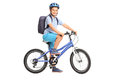Studio shot of a schoolboy riding a bicycle and looking at the camera isolated on white background Stock Photo