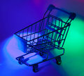 Studio shot of shopping cart in multicolor light Royalty Free Stock Photo