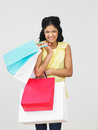 Studio shot of teenage girl with shopping bags smiling to camera Royalty Free Stock Photo