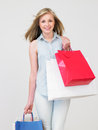 Studio shot of teenage girl with shopping bags smiling to camera Royalty Free Stock Photography