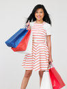 Studio shot of teenage girl with shopping bags smiling to camera Royalty Free Stock Photos