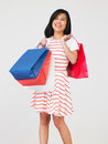 Studio shot of teenage girl with shopping bags smiling to camera Royalty Free Stock Image