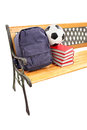 Studio shot of a wooden bench with books school bag and footbal football on it isolated on white background Royalty Free Stock Photos