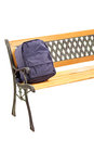 Studio shot of a wooden bench with school bag on it isolated white background Royalty Free Stock Image