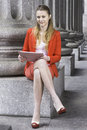 Study outside dressing in a red blazer a light red skirt fashionable shoes a young student is sitting and studying Stock Images