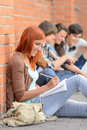 Studying girl writing notes friends sitting background in row on ground Stock Image